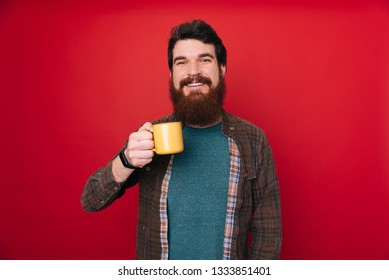 Picture of cheerful bearded man standing with cup of coffee isolated over red background.
