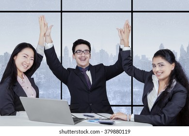 Picture of cheerful businesspeople clapping hands together in the office to celebrate a good job