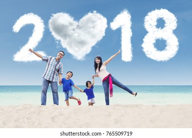 Picture of cheerful family playing together in the shore with clouds shaped numbers 2018 and heart in the sky