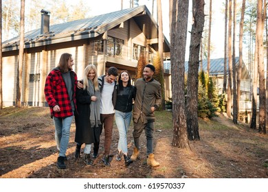 Picture of cheerful group of friends walking outdoors in the forest. Looking aside.