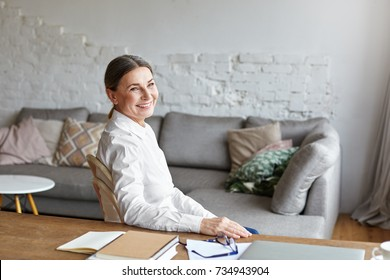 Picture of cheerful middle aged school psychologist having rest at her study, sitting at desk with copybook, notes and laptop computer. Beautiful senior female freelancer taking notes working at home