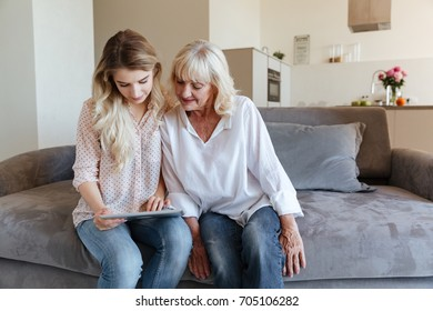 Picture of cheerful young lady sitting at home with her grandmother using tablet computer. Looking aside.