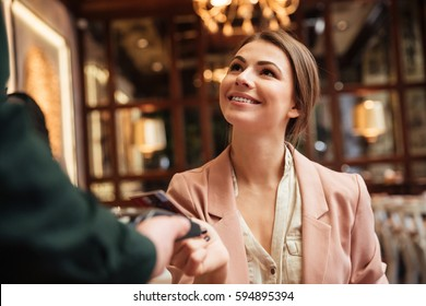 Picture of cheerful young pretty woman sitting in cafe. Looking at man waiter while pays the order with credit card.