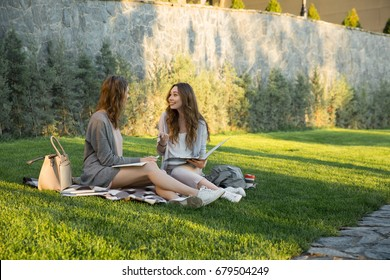 Picture of cheerful young two women sitting outdoors in park writing notes. Looking aside.
