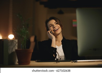 Picture of cheerful young woman designer sitting indoors at night using computer and talking by phone. Looking aside.