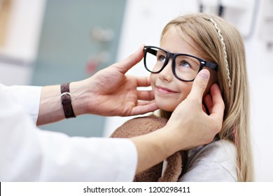 Picture of child optometry male optometrist optician doctor examines eyesight of little girl