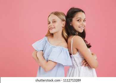Picture closeup of brunette and blonde female friends wearing dresses smiling and looking at camera while standing back to back with arms crossed isolated over pink background