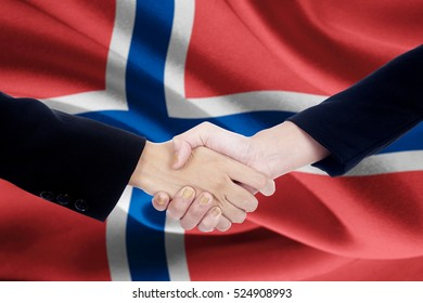 Picture of a collaboration handshake with two people hands, closing a meeting and shaking hands with flag of Norway