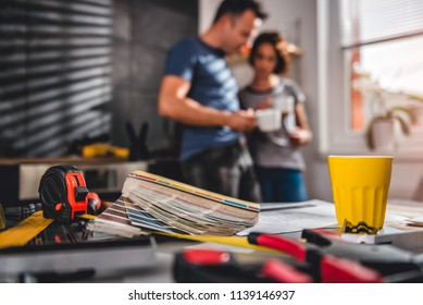 Picture of color swatch with tape measure on the table in the kitchen with couple standing in the background