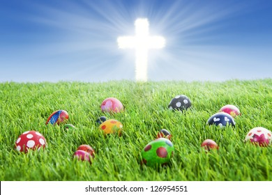 Picture of colorful easter eggs laying on the grass with a bright Cross