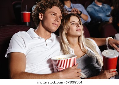 Picture of concentrated young friends loving couple sitting in cinema watch film drinking aerated sweet water.