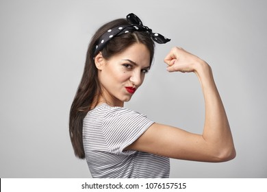 Picture of confident attractive young woman with dark loose hair and athletic slim body posing isolated at studio wall, demonstrating her strength and muscles, tensing bicep, staring at camera