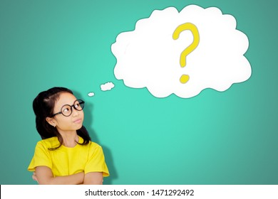 Picture of confident schoolgirl looking at a cloud bubble with a question mark in blackboard in the classroom