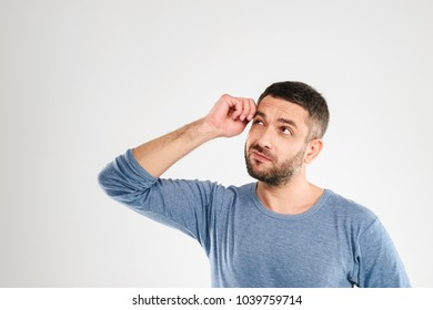 Picture of confused man standing isolated over white background wall. Looking aside.