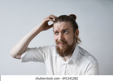 Picture of confused and puzzled young Caucasian office worker with beard and hair knot scratching his head, having clueless and worried look, trying hard to recollect something. Body language