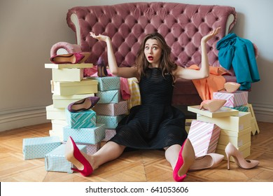 Picture of confused young lady sitting on floor near sofa indoors choosing shoes. Looking at camera.