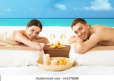 picture of couple on the beach drinking champagne