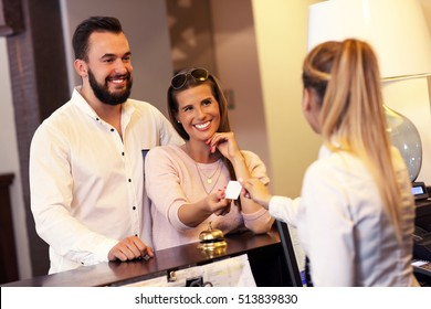 Picture of couple and receptionist at counter in hotel