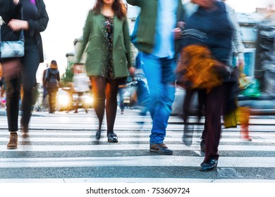 picture of crowds of people in motion blur crossing a city street