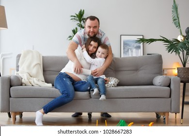 Picture of cuddling family with son on gray sofa