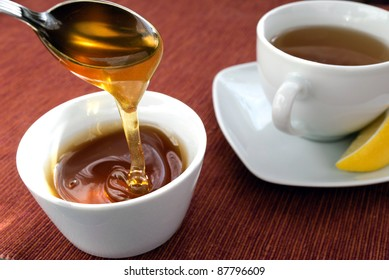 Picture of a cup of green tea with lemon and cup of honey.
