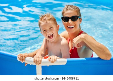 Picture of cute boy with his mother playing in a pool of water during the summer