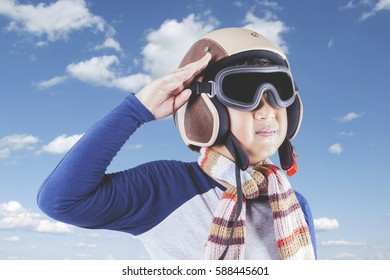 Picture of a cute boy wearing an aviator helmet and showing a saluting gesture, shot outdoors