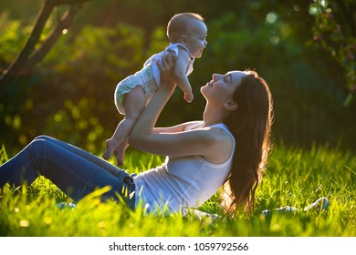 Picture of cute cheerful baby on mother's hands outdoors