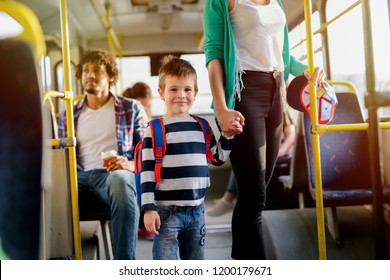 Picture of cute little boy in a bus. Looking at he camera and holding his mothers hand.