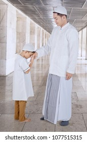Picture of cute little boy wearing Islamic clothes while kissing hand of his father in the mosque