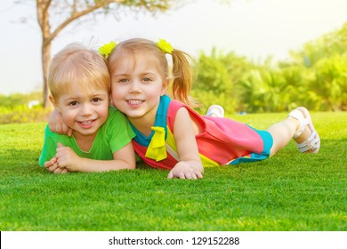 Picture of cute little girl with pretty boy lying down on green grass in park, cheerful children resting on the field on backyard, brother and sister having fun outdoors in springtime, happy childhood