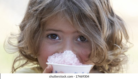 a picture of a cute little girl smiling eating snow cone