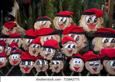 Picture of Tió de Nadal, or Christmas Log. A hollow log wearing barretina, called called Caga tió, or Shitting log /Poo log. Wood Christmas decoration sell on xmas markets. Catalan Christmas tradition