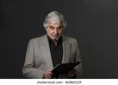 Picture of demanding professor man of university or college isolated on black background. Mature teacher posing with clipboard and looking at camera in studio.