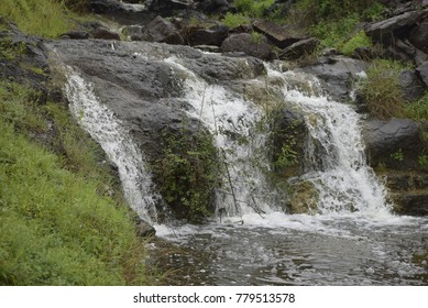 A picture depicting small waterfall with green background in rainy season