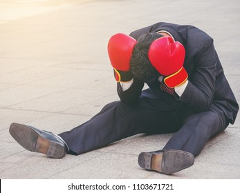 Picture of depressed businessman sitting on path outside office with red glove as a surrender action. Unsuccessful or failure business.