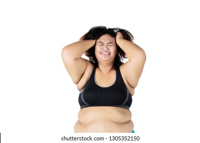 Picture of depressed fat woman wearing sportswear while scratching her head, isolated white background