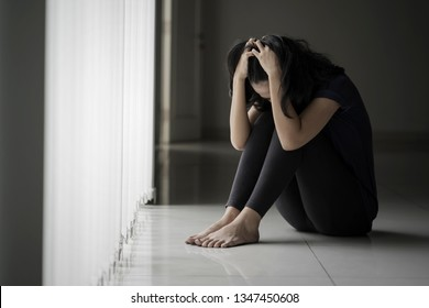 Picture of a desperate woman scratching her head while sitting near the window in black background