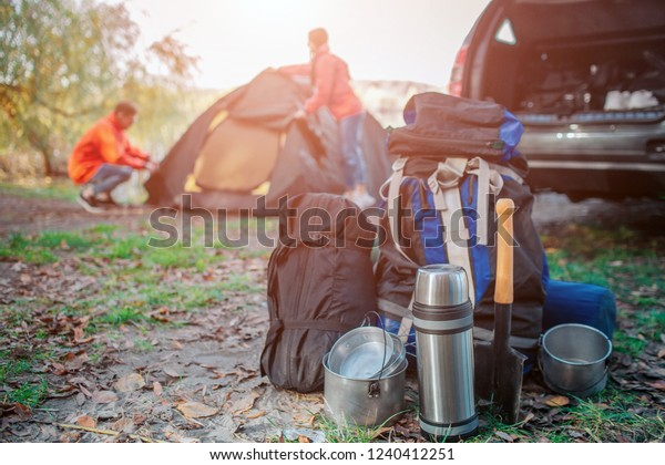 Picture of different expedition equipment. There are backpack with carimate, sleeping bag and dishes. Young man and woman are packing tent. They are at car.