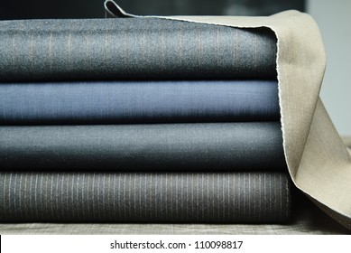 Picture of different rolled fabrics set up in stack.