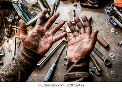 A picture of dirty hands of a guy from the garage. Hard and dirty work is behind him.