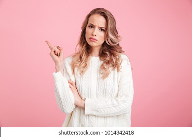 Picture of displeased young woman standing isolated over pink background. Looking camera pointing.