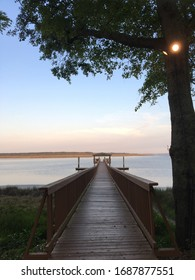 The picture of the Dock in the early morning on the Hilton Head Island. The Wooden Long path end with small gazebo at the end facing calm water, sunrise, beautiful sky. Good place to start water sport