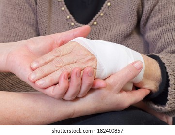 Picture of doctor's hand making a bandage for an elderly hand
