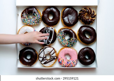 Picture of doughnut box with a child's hand grabbing a doughnut