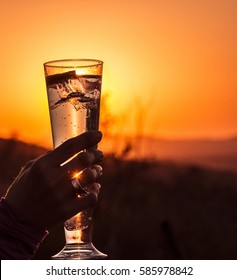 Picture of a drink with sunset as  background (sundowner) in South Africa.