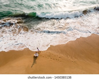 Picture from drone newlywed couple walking along beautiful beach. Scenic aerial view of Happy romantic couple waking together near the ocean. Wedding on the beach