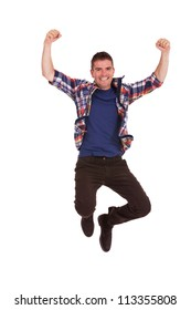 Picture of an ecstatic casual young man, jumping in the air and smiling, with hands raised