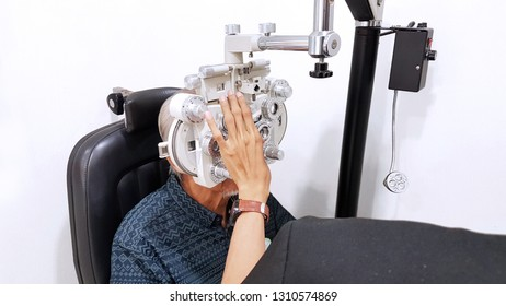 Picture of elderly man examining his eyes by using a phoropter while visiting optometrist in the hospital