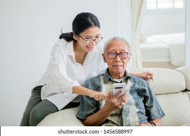 Picture of elderly man using a digital tablet with his daughter while sitting together on the couch